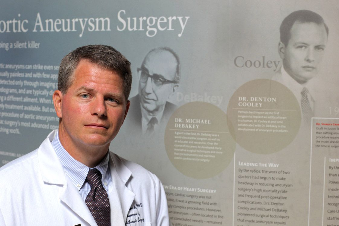 Physician standing in front of Aortic Aneurysm sign.
