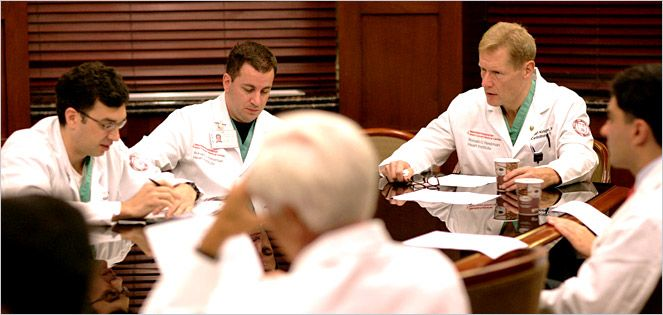 Physicians in white lab coats hold a meeting at a conference room table.