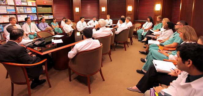 Residents sit around a conference room table in a discussion.